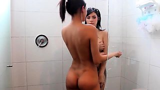 Two playful teens indulge in lesbian action in the shower