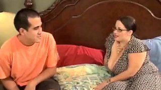 chubby brunette with big tits and glasses on bed